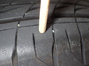 タイヤのトレッド部を竹の棒で押しているところ