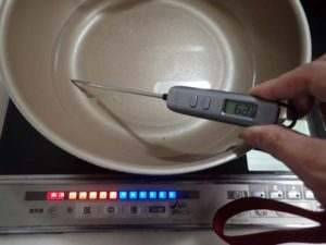 IHで加熱中のフライパンの底の温度を測っている様子