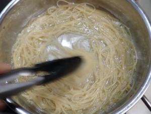 パスタを茹でた鍋の中で乳化させている様子