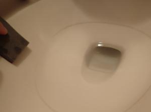 アズマジックでトイレの尿石を削り取っている様子