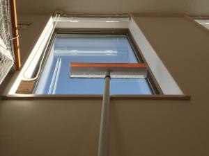 水切りワイパーで高所のガラス窓を掃除している様子