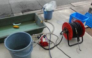 屋外に用意された分解したエアコンのパーツを洗浄するための洗浄器具