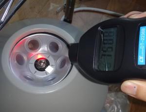 回転部に反射テープを貼り、回転計を使って回転数を測定しているところ