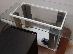 ガラス水槽の4隅に吸音材を設置して定在波を防止する実験をしている様子