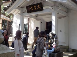 豊川稲荷の大黒堂前 大国天をさする参拝客